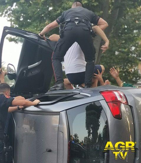 Ostia, i carabinieri si calano nei veicolo rovesciato e salvano due persone