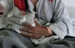 una mamma sorridente con il bambino in bracco